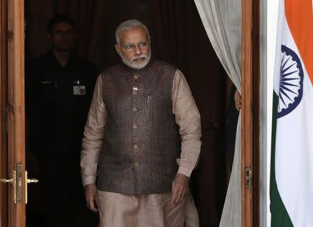 India's PM Modi comes out of a meeting room to receive his Bhutanese counterpart Tobgay before the start of their bilateral meeting in New Delhi