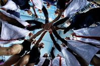 In this photo taken with a fisheye lens, Britain women's water polo players huddle before the seventh place water polo match at the 2012 Summer Olympics, Thursday, Aug. 9, 2012, in London. (AP Photo/Julio Cortez)