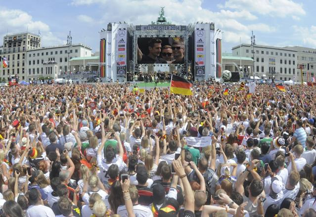 """Germany's national football team players (L-R) pictured on a giant screen as fans gather at the """"Fanmeile"""" area in front of Berlin's Brandenburg Gate to welcome the victorious German national football team on July 15, 2014 (AFP Photo/Robert Michael)"""