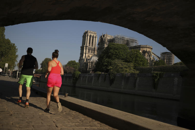 Two people jog under a bridge by a the Notre Dame Cathedral in Paris, Saturday, April 20, 2019. Rebuilding Notre Dame, the 800-year-old Paris cathedral devastated by fire this week, will cost billions of dollars as architects, historians and artisans work to preserve the medieval landmark. (AP Photo/Francisco Seco)