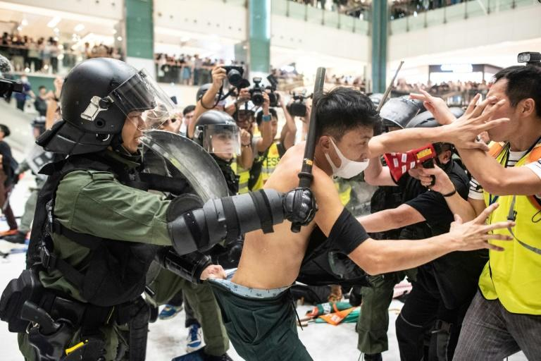 Police officers try to apprehend a man inside a mall during Sunday's clashes
