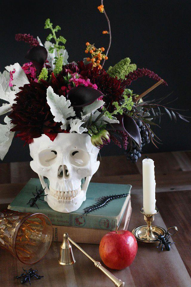 """<p>Create the ultimate Halloween display with a faux skull filled with bewitching flowers, a stack of vintage spell books, a dangerous dripping candle, and a potentially poisonous apple.<br></p><p><strong>Get the tutorial at <a href=""""http://honestlyyum.com/11584/diy-floral-skull-centerpiece/"""" rel=""""nofollow noopener"""" target=""""_blank"""" data-ylk=""""slk:Honestly Yum"""" class=""""link rapid-noclick-resp"""">Honestly Yum</a>.</strong></p><p><strong><a class=""""link rapid-noclick-resp"""" href=""""https://www.amazon.com/Gift-Pro-Ceramic-Succulent-Containers/dp/B06XZPP2LP/ref=sr_1_1?tag=syn-yahoo-20&ascsubtag=%5Bartid%7C10050.g.3739%5Bsrc%7Cyahoo-us"""" rel=""""nofollow noopener"""" target=""""_blank"""" data-ylk=""""slk:SHOP SKULL VASE"""">SHOP SKULL VASE</a></strong></p>"""