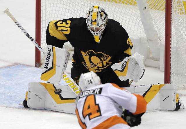 Philadelphia Flyers' Sean Couturier (14) gets the game-winning goal past Pittsburgh Penguins goaltender Matt Murray (30) in overtime of an NHL hockey game in Pittsburgh, Sunday, March 17, 2019. The Flyers won 2-1. (AP Photo/Gene J. Puskar)