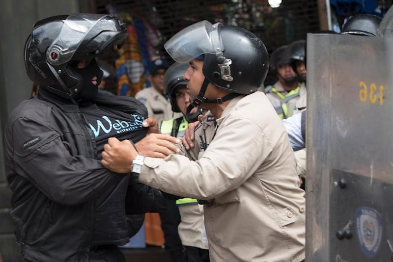 A Venezuelan pro-government supporter scuffles with riot police in Caracas, on March 31, 2017 (AFP Photo/)