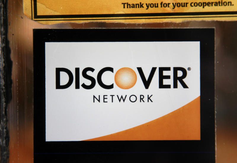 FILE-In this Monday, Sept. 24, 2012, file photo, a Discover logo is adhered to a window at the entrance of a shop in Cambridge, Mass. Discover Financial Services said Thursday, Sept. 27, 2012, its net income fell 3 percent in its fiscal third quarter, but the result beat Wall Street expectations as credit card use increased and more customers paid off their card balances on time. (AP Photo/Steven Senne, File)