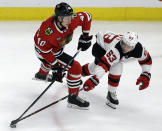 Chicago Blackhawks right wing John Hayden, left, shoots against New Jersey Devils left wing Jesper Bratt during the second period of an NHL hockey game Thursday, Feb. 14, 2019, in Chicago. (AP Photo/Nam Y. Huh)