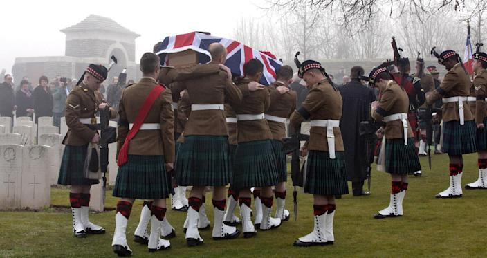 Members of a Scottish Division Firing Party hold their rifles inverted, in a sign of respect, as pallbearers carry the casket of British World War One soldier William McAleer during a reburial service at the Loos British World War One cemetery in Loos-en-Gohelle, France on Friday, March 14, 2014. Private William McAleer, of the 7th Battalion, Royal Scots Fusiliers, was killed in action on Sept. 26, 1915 during the Battle of Loos. His body was found and identified in 2010 during routine construction in the area and is being reburied with full military honors along with 19 unknown soldiers. (AP Photo/Virginia Mayo)