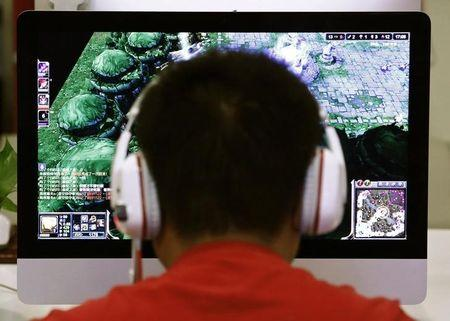 A man plays a computer game at an internet cafe in Beijing