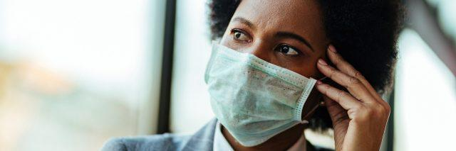 woman wearing a face mask, looking stressed