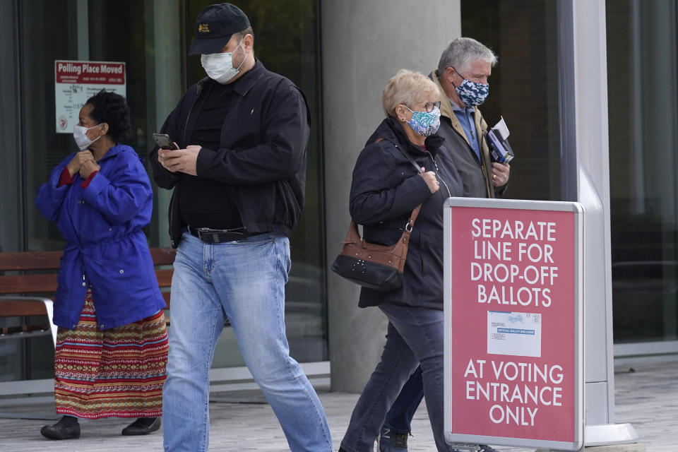 People wear mask as they leave at Indian Trails Public Library after voting in Wheeling, Ill., Wednesday, Oct. 21, 2020. (AP Photo/Nam Y. Huh)