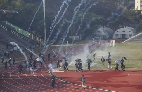Officers fire tear gas at students on a CUHK sports ground. Photo: Winson Wong