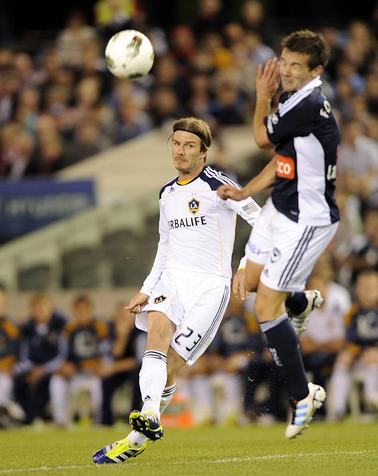 David Beckham, left, of the LA Galaxy kicks the ball during their soccer friendly match against the Melbourne Victory in Melbourne, Australia, Tuesday, Dec. 6, 2011. ( AP Photo/Andrew Brownbill)