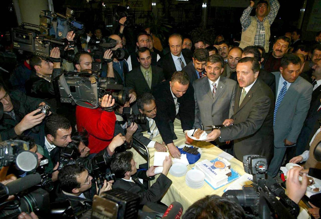 <p>Turkey's Justice and Development Party (AKP) leader Recep Tayyip Erdogan (R), flanked by his deputy Abdullah Gul (2nd-R) offers cake to members of the media, at the party headquarters in Ankara, early November 4, 2002, after his party claimed victory in Turkish elections. (Stringer/Reuters) </p>