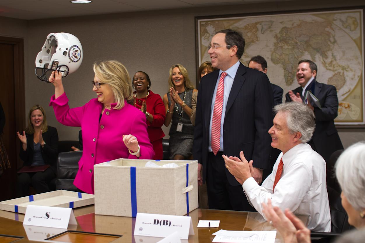 This photo provided by the United States Department of State shows Secretary of State Hillary Rodham Clinton holding up a football helmet presented to her at the State Department in Washington, Monday, Jan. 7, 2013, as she returned to work after a month-long absence caused first by a stomach virus, then a fall and a concussion and finally a brief hospitalization for a blot clot near her brain. (AP Photo/United States Department of State)