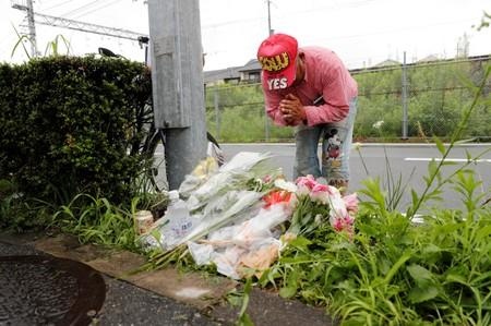 A man prays after placing flowers near the torched Kyoto Animation building to mourn the victims of the arson attack in Kyoto