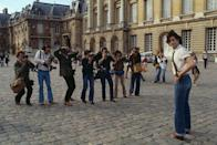 <p>The '70s heartthrob gives a cheeky grin to the camera at the Palace of Versailles. That very same year, Travolta would go on to become a household name when <em>Grease</em> was released.</p>