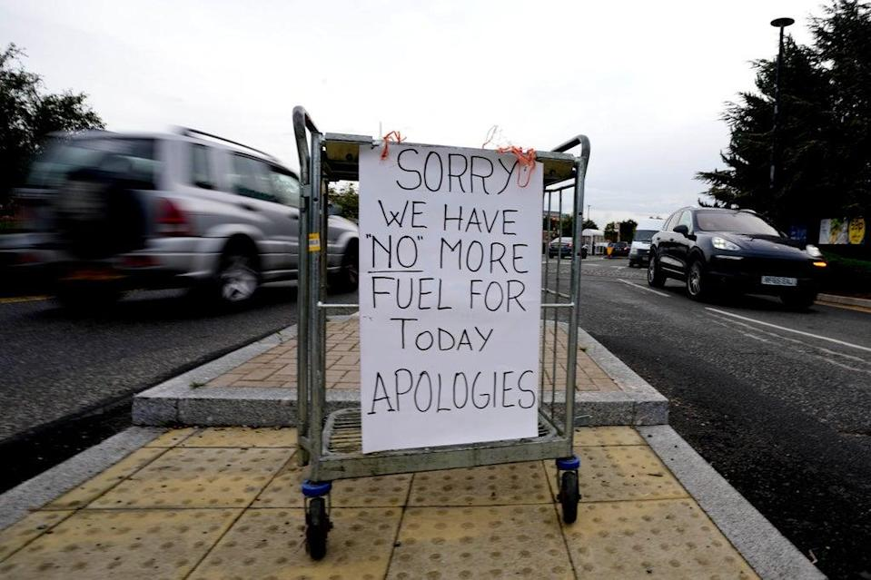A sign referring to the lack of fuel is placed at the entrance to a petrol station in London on Tuesday  (AP)