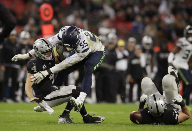 FILE - In this Oct. 14, 2018, file photo, Oakland Raiders quarterback Derek Carr (4) is sacked by Seattle Seahawks defensive end Frank Clark (55) during the second half of an NFL football game at Wembley stadium in London. After being well protected his first four seasons, Carr has been under heavy pressure the past few weeks and the results have not been good. (AP Photo/Matt Dunham, File)
