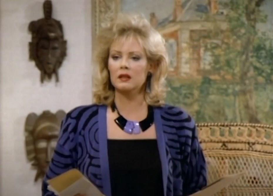 A woman(Jean Smart) holding envelopes and letters in her both hands