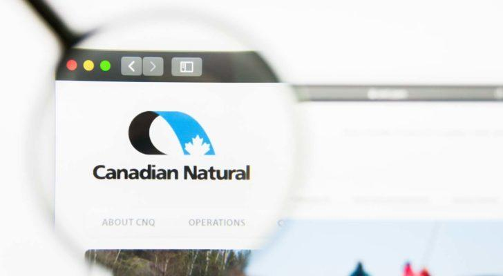 A magnifying glass zooms in on the website for Canadian Natural Resources (CNQ).