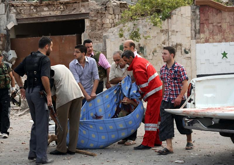 In this photo released by the Syrian official news agency SANA, Syrian men carry a dead body at the scene where triple bombs exploded at the Saadallah al-Jabri square, in Aleppo city, Syria, Wednesday Oct. 3, 2012. Three powerful explosions rocked the main square in a government-controlled central district of Aleppo on Wednesday, the Syrian state-run TV said. Activists reported multiple casualties and heavy material damage. (AP Photo/SANA)