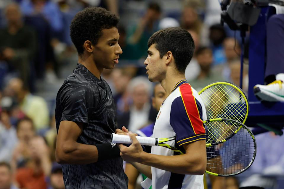 Felix Auger-Aliassime shakes hands with Carlos Alcaraz after Alcaraz abruptly retired in the second set of their Round of 16 match.