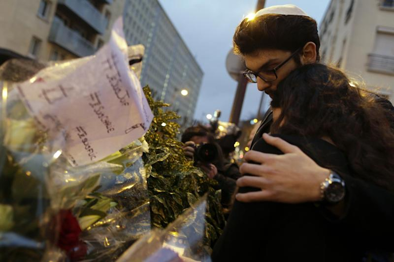 Mourners stand in front of flowers during a gathering at the end of Shabbat called by the Jewish Student's Union of France (UEJF) association on January 10, 2015, at the Porte de Vincennes in eastern Paris