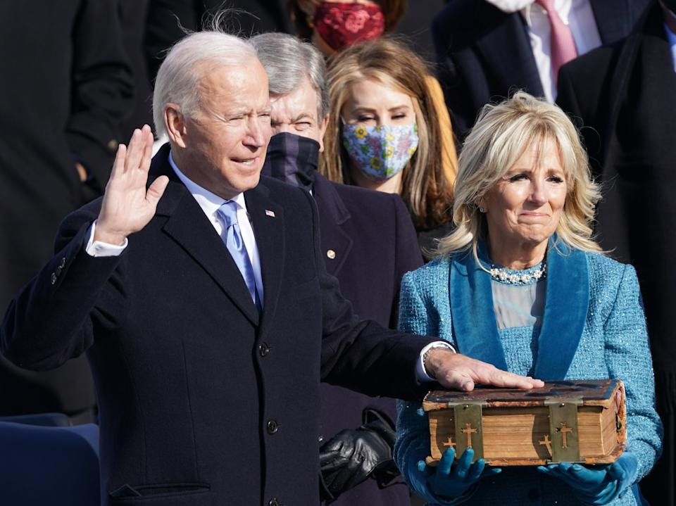 Joe Biden is sworn in as the 46th president of the United States on the West Front of the Capitol while his wife Jill Biden holds a bible. The president welcomed a 'day of history and hope' after taking the oath of office saying: 'This is America's day. This is democracy's day.'REUTERS