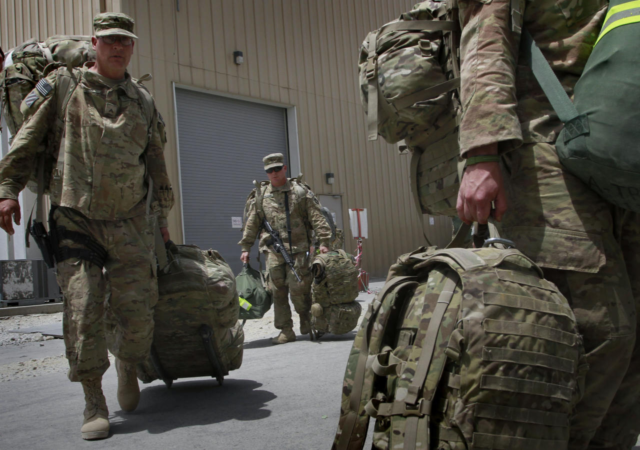 FILE -- In this Thursday, July 14, 2011 file photo, U.S. soldiers with Task Force Red Horse carry their baggage to the customs office for checking, as they leave Afghanistan at the U.S. base in Bagram north of Kabul, Afghanistan. The United States is not alone in pulling combat troops off the Afghan battlefield. More than a dozen other countries have draw down plans that combined with the U.S. withdrawal will shrink the foreign military footprint in Afghanistan by more than 40,000 troops by the close of next year. (AP Photo/Musadeq Sadeq, File)