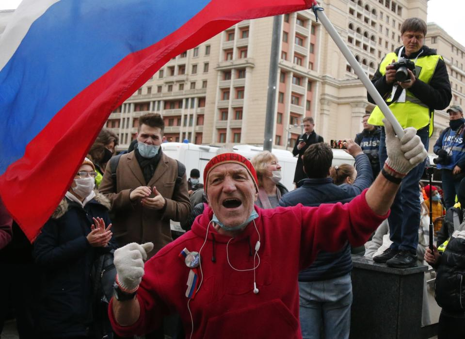 A supporter waves Russian flag and shouts slogans during the opposition rally in support of jailed opposition leader Alexei Navalny in Moscow, Russia, Wednesday, April 21, 2021. Police across Russia have arrested more than 180 people in connection with demonstrations in support of imprisoned opposition leader Alexei Navalny, according to a human rights group. (AP Photo/Alexander Zemlianichenko)