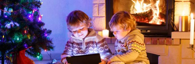 Two young boys looking at a tablet by a fireplace and Christmas tree.