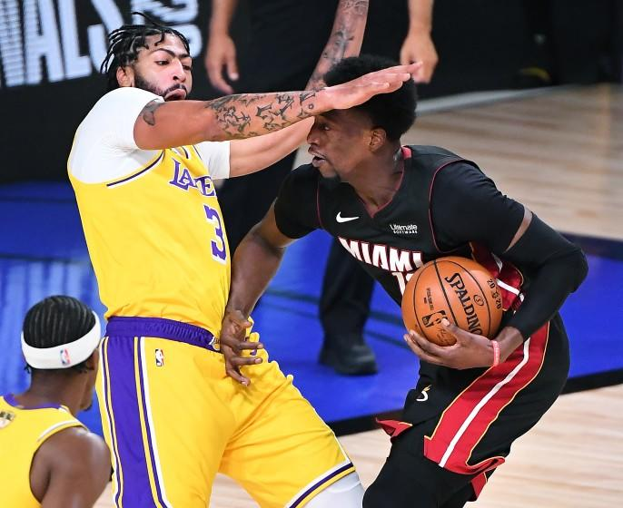 ORLANDO, FLORIDA OCTOBER 6, 2020-Heat's Bam Adebayo charges into Lakers Anthony Davis for a foul in the 1st quarter in Game 4 of the NBA FInals in Orlando Sunday. (Wally Skalij/Los Angeles Times)