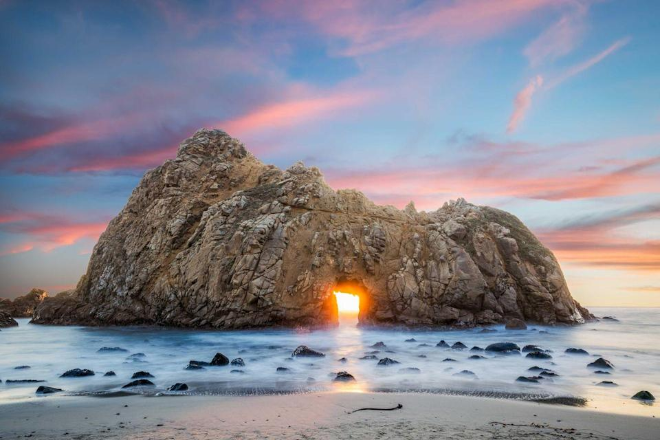"<p>The glowing sun appears in the ""keyhole"" of the Pfeiffer Beach rock in Big Sur, California.</p>"