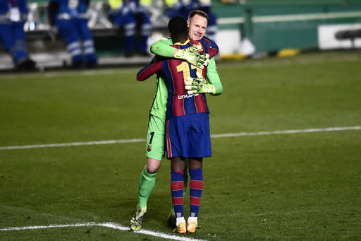 Barcelona's goalkeeper Marc-Andre ter Stegen greets teammate Ousmane Dembele, front, during Spanish Super Cup semi final soccer match between Barcelona and Real Sociedad at Nuevo Arcangel stadium in Cordoba, Spain, Wednesday, Jan. 13, 2021. Barcelona will play the final after defeating Real Sociedad 3-2 in a penalty shootout after the game ended 1-1. (AP Photo/Jose Breton)