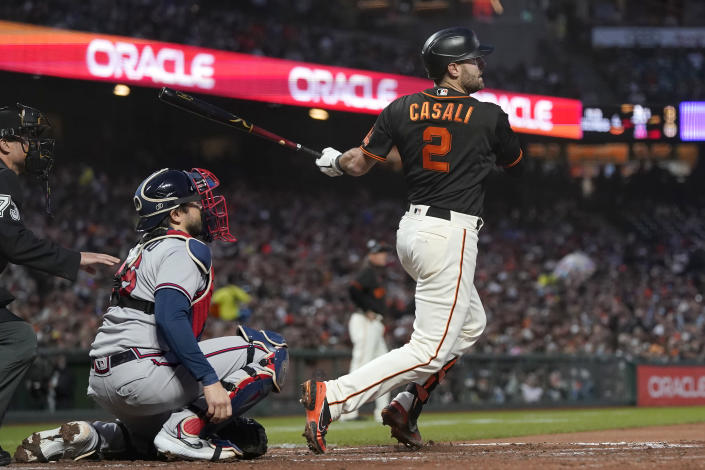 San Francisco Giants' Curt Casali (2) hits a two-run single in front of Atlanta Braves catcher Travis d'Arnaud during the fourth inning of a baseball game in San Francisco, Saturday, Sept. 18, 2021. (AP Photo/Jeff Chiu)