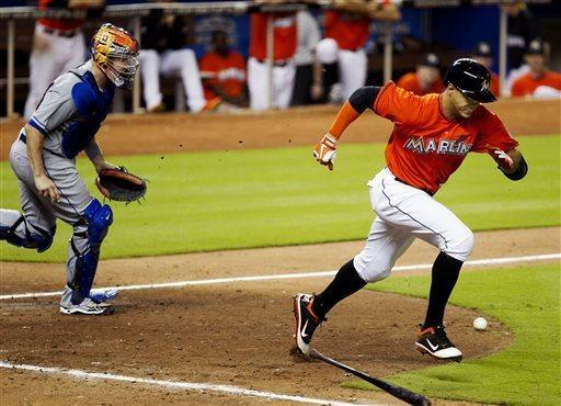 Miami Marlins' Giancarlo Stanton follows through on his hit as New York Mets catcher John Buck heads out during the 10th inning of a baseball game at Marlins Park in Miami on Monday, April 29, 2013. (AP Photo/The Miami Herald, Joe Rimkus Jr.)