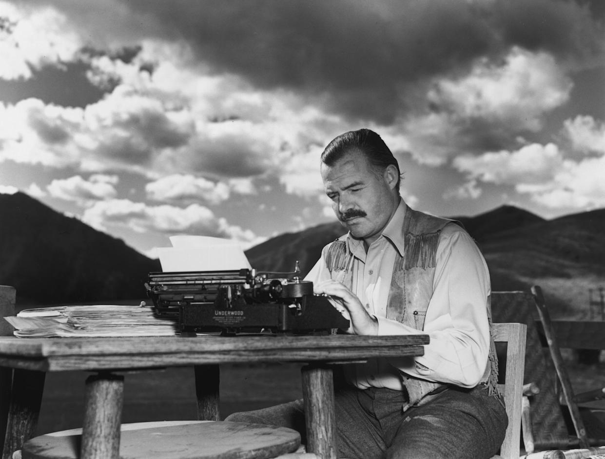 Ernest Hemingway (1899 - 1961) works at his typewriter while sitting outdoors, Idaho. (Photo by Lloyd Arnold/Hulton Archive/Getty Images)