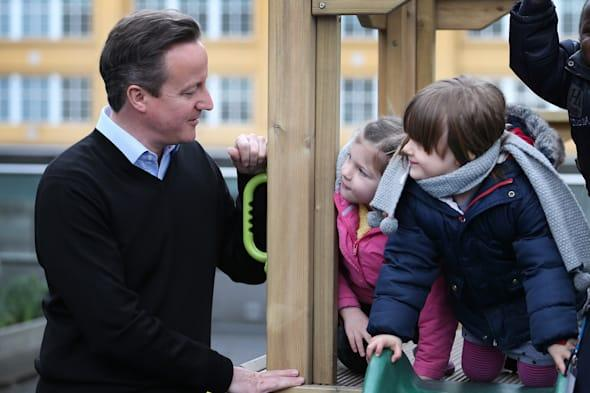 Children look at Prime Minister David Cameron during a visit to the Coin Street nursery in London, as the government have announced a new tax-free childcare allowance worth up to £2,000 per child -  to start after the 2015 general election. PRESS ASSOCIATION Photo. Picture date: Tuesday March 18, 2014. See PA story POLITICS Budget. Photo credit should read: Peter Macdiarmid/PA Wire