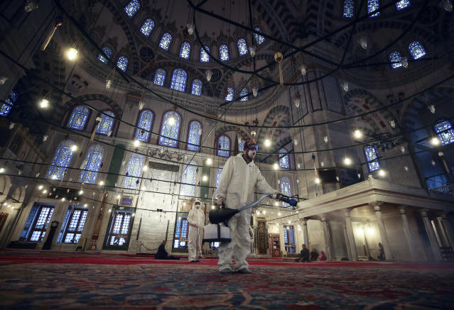 A worker wearing protective clothing disinfects historical Fatih Mosque, in Istanbul, Saturday, March 14, 2020, as a precaution against the coronavirus. For most people, the new coronavirus causes only mild or moderate symptoms. For some it can cause more severe illness.(AP Photo/Emrah Gurel)