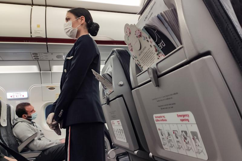 A flight attendant, cabin crew of Aegean Airlines wearing protective mask and gloves as a preventive measure against the spread of the COVID-19 at Athens International Airport ATH LGAV in Athens, Greece on March 17, 2020. Greece and Europe closed the borders for people outside of Europe and the Schengen zone, arriving travellers will be required to quarantine for 14 days. Greece has 418 patients and 4 fatal cases. March 17, 2020 (Photo by Nicolas Economou/NurPhoto via Getty Images)