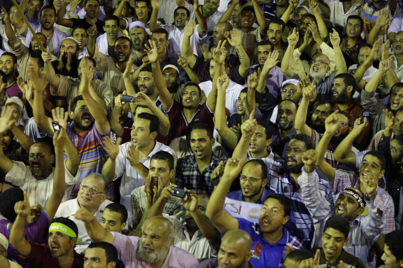 Supporters of Egypt's ousted President Mohammed Morsi shout slogans during a demonstration in front of Cairo University, where protesters have installed their camp in Giza, southwest of Cairo, Egypt, late Wednesday, July 17, 2013. The European Union's top foreign policy official urged Egypt's interim leaders and supporters of the ousted Islamist president Wednesday to cooperate in a political process that moves the country toward democracy. But Morsi's backers expanded their protests in Cairo, denouncing the new government and casting doubt on the prospects for reconciliation. (AP Photo/Hussein Malla)