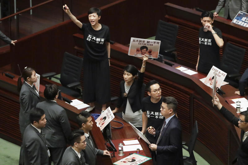 In this Wednesday, Oct. 16, 2019, file photo, pro-democracy lawmakers protest as Hong Kong Chief Executive Carrie Lam delivers a speech at chamber of the Legislative Council in Hong Kong Wednesday, Oct. 16, 2019. Chanting pro-democracy lawmakers have interrupted the start of a speech that Lam was giving laying out her policies. (AP Photo/Mark Schiefelbein, File)