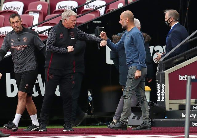 Guardiola (right) feels describing City as Europe's best, as David Moyes (left) believes, is premature