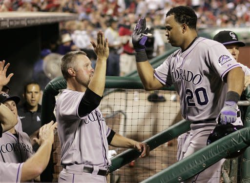 Colorado Rockies' Wilin Rosario, right, is greeted in the dugout by Michael Cuddyer, left, after Rosario's two-run home run in the ninth inning of a baseball game with the Philadelphia Phillies, Thursday, June 21, 2012, in Philadelphia. The Rockies won 4-1. (AP Photo/Tom Mihalek)