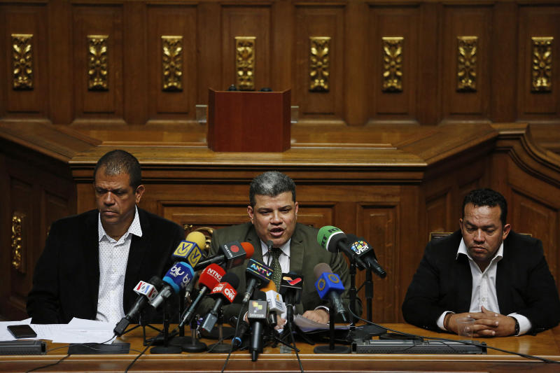 Lawmakers Luis Parra, center, Franklyn Duarte, right, and Jose Noriega, left, give a press at the National Assembly in Caracas, Venezuela, Monday, Jan. 6, 2020. The previous day, lawmakers loyal to President Nicolas Maduro rushed to choose Parra as their new legislative president, while many opposition lawmakers were blocked from entering the voting session. (AP Photo/Andrea Hernandez Briceño)