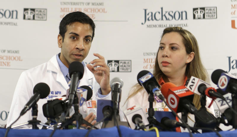 Dr. Urmen Desai, left, talks to reporters as Dr. Wrood M. Kassira, both plastic surgeons, looks on during a news conference in Miami, Tuesday, May 21, 2013. The doctors gave an update on the progress of Ronald Poppo, a homeless man whose face was mostly chewed off in a bizarre attack last year in Miami. The attack left Poppo blind, but the doctors say he's been working with an occupational therapist to learn how to take care of himself. The doctors say Poppo also has learned to play guitar and practices daily. (AP Photo/Alan Diaz)