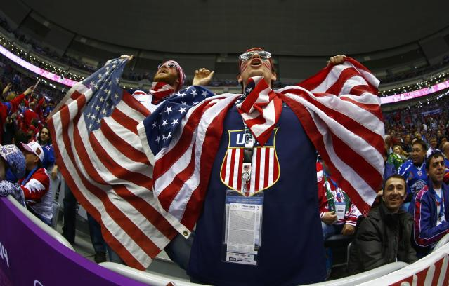 Fans hold U.S. flags during the men's preliminary round hockey game between Russia and USA at the Sochi 2014 Winter Olympic Games February 15, 2014. REUTERS/Mark Blinch (RUSSIA - Tags: OLYMPICS SPORT ICE HOCKEY)
