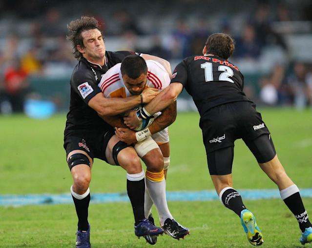 New Zealand Waikato Chiefs' Liam Messam (C) is tackled by Durban Sharks Keegan Daniels (L) during a Super 15 rugby union match at the Mr Price Kings Park Rugby Stadium on April 21, 2012. AFP PHOTO (Photo credit should read -/AFP/Getty Images)