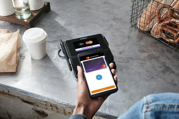 Person using mobile device to pay with a mastercard in a coffee shop.
