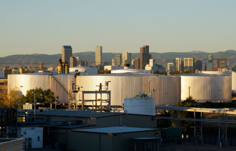 Oil storage tanks are seen at sunrise with the Rocky Mountains and the Denver downtown skyline in the background